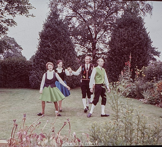 A group of four dancing on a lawn