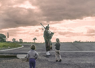 A piper watched by two children