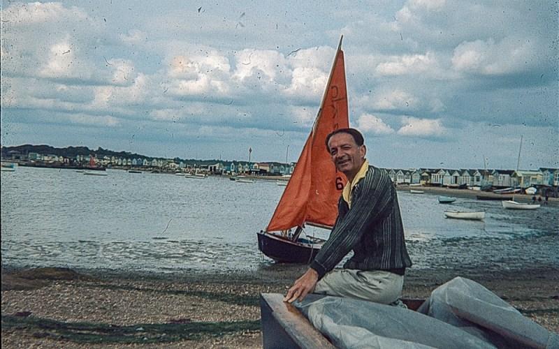 A man sitting on a boat on a beach