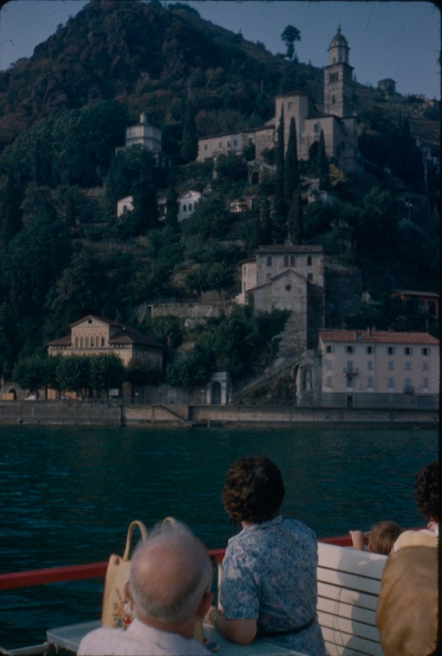 People on a boat looking at a castle build into the side of a hill on a Swiss lake