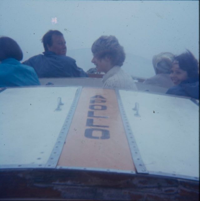 A photo of a family in a fairground ride with Apollo written on it