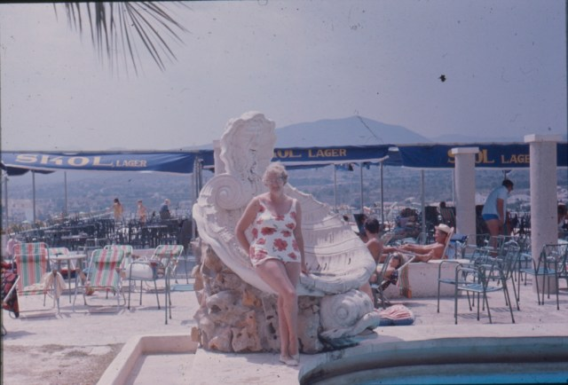 A woman posing for a picture at the side of a pool