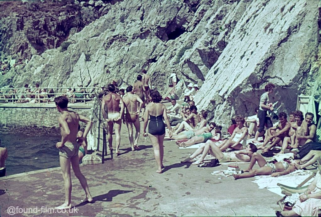 People sunbathing at the bottom of a rock face by the sea