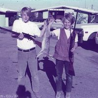 Two boys with guns and a dead rabbit