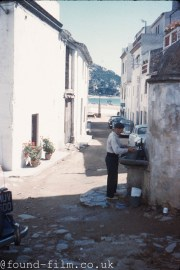 Man filling a kettle in a narrow Spanish street - 1958
