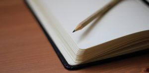 A notebook with a pencil on top
