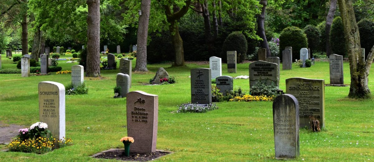 several gravestone in front of trees
