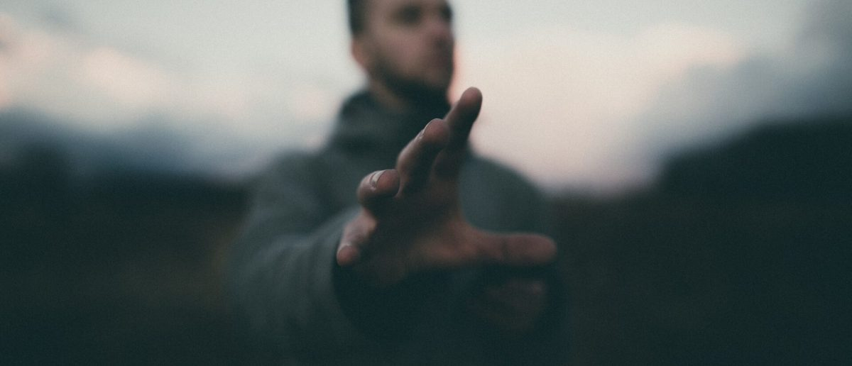 hand reaching out with man blurred in the background