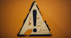 A warning sign fading on a wall