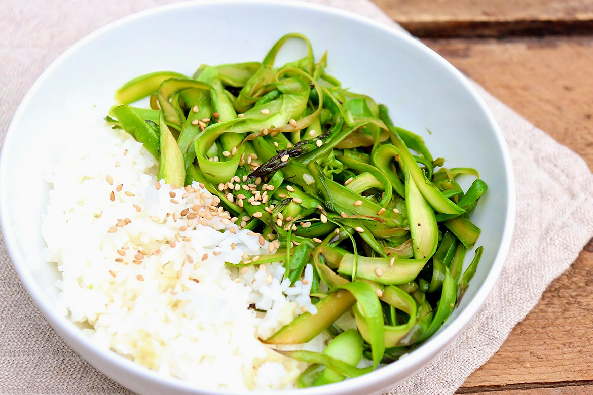 Thin slivers of asparagus and a super simple sauce are the key components of this delightful dish that, when served over rice, stands somewhere between comfort food and culinary bliss. Feel free to experiment with other vegetables like zucchini, snap peas, Brussels sprouts, and even broccoli.
