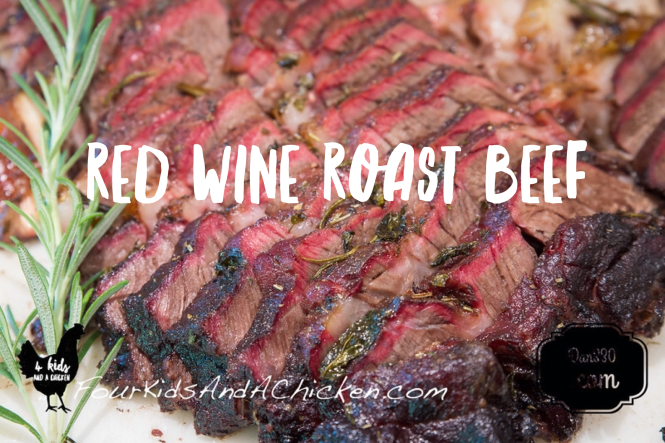 Red wine roast beef show sliced next to rosemary so that the fresh green of the herb balances with the smoke rings of the meat.