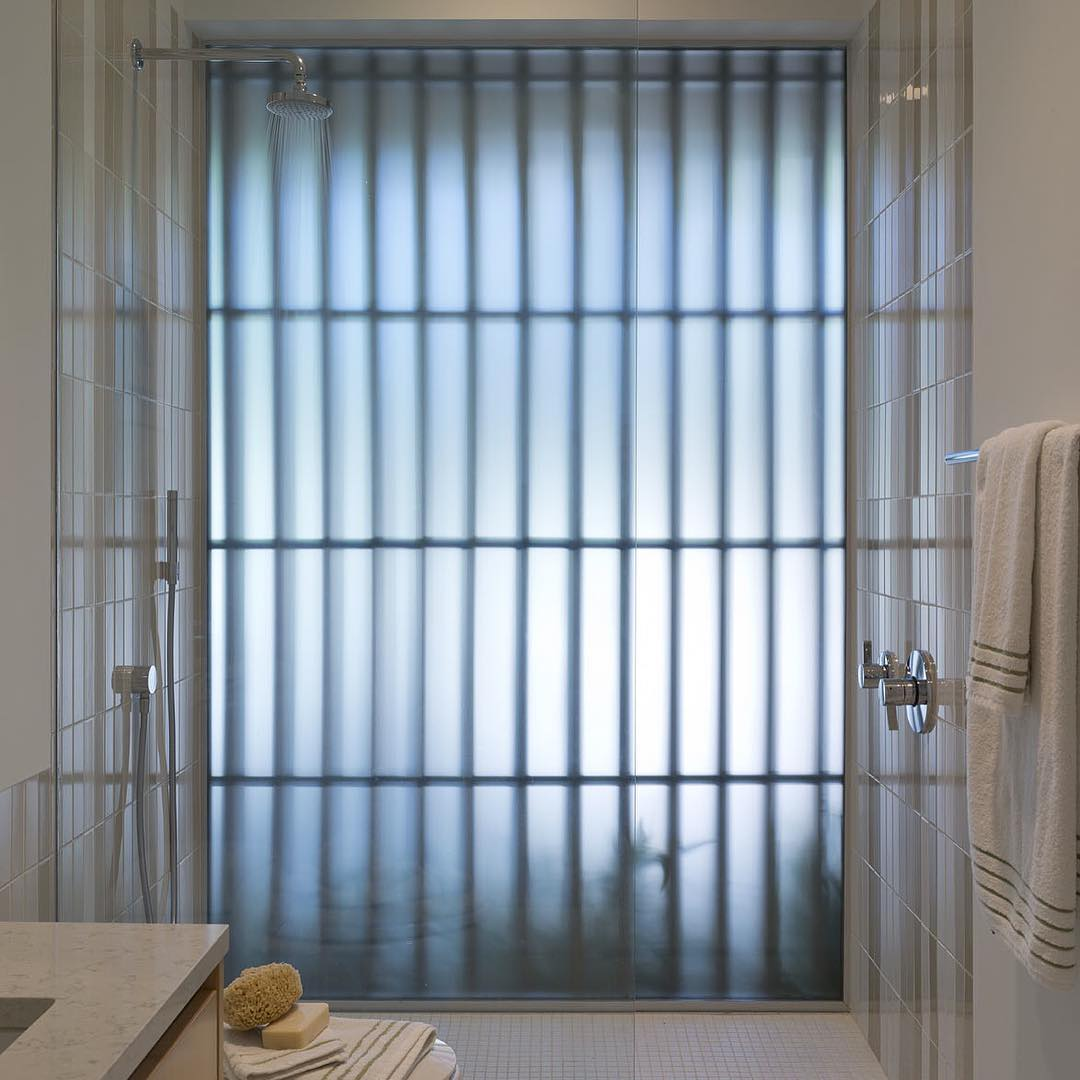 @webberstudio designed bathroom with full glass exterior shower wall and cypress privacy screen. Built by @foursquarebuilders