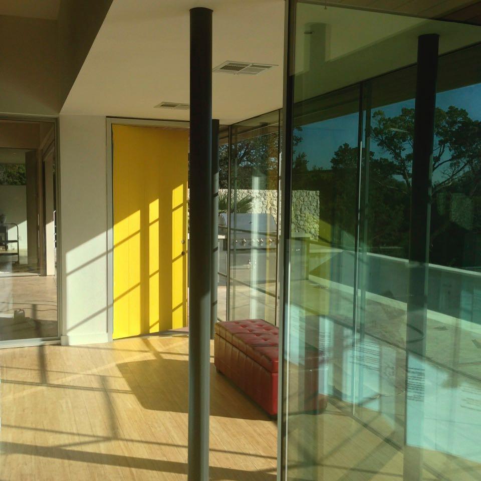 Yellow front door by @webberstudio Walls of glass by @foursquarebuilders