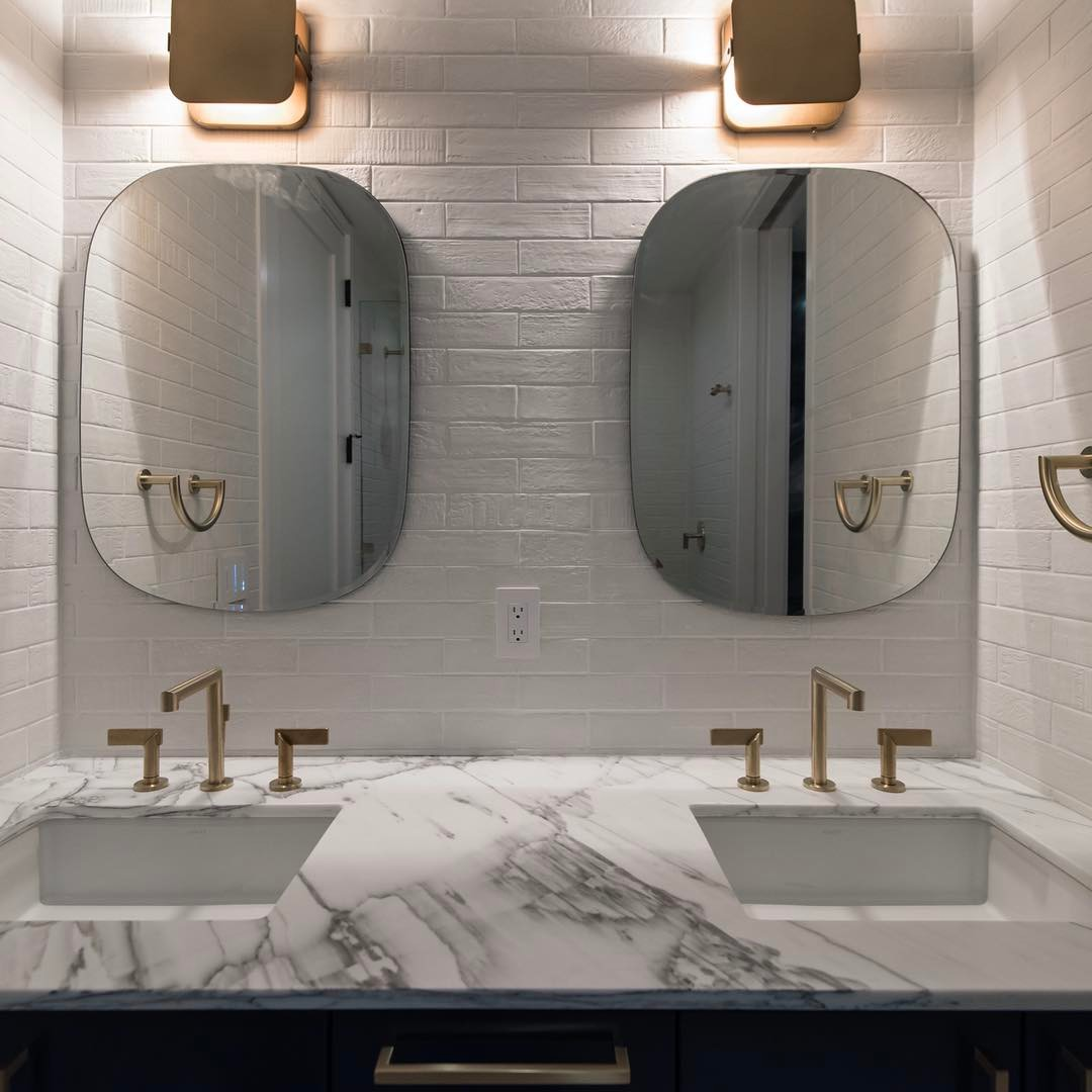 Newport brushed brass faucets against Emil Ceramica tile walls. Designed by @slicdesign Built by @foursquarebuilders Photo by @redpantsstudio