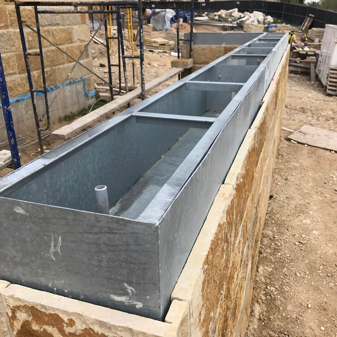 Galvanized steel planters to be hidden in stone wall. Built by @foursquarebuilders