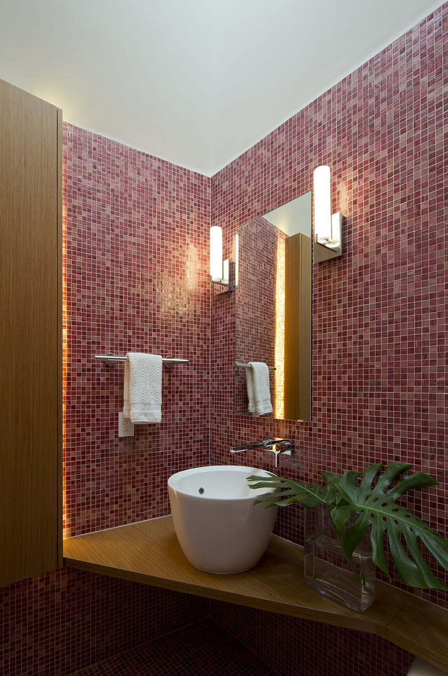 Powder bath welcomes guests with mosaic tile and floating vanity.
