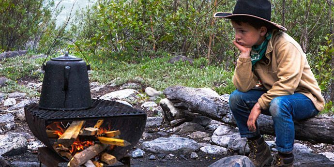 A young boy in a cowboy outfit and sitting on a log looks at a kettle over a fire, one method described in Fourth Estate's article on how to make coffee without a coffee maker.