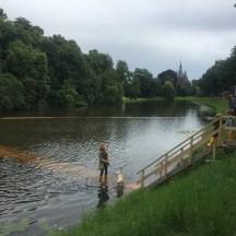 onderwater brug met mensen en hond, kerk in verte