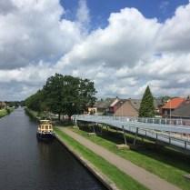 gele en blauwe boot in kanaal vanaf fietsbrug