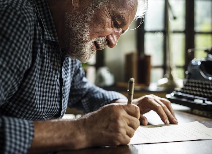 Elderly man writing a letter.