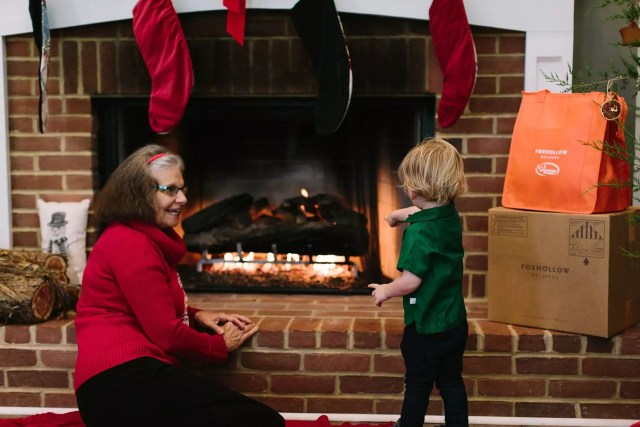 Grandmother and Child Stay Warm by a Fire