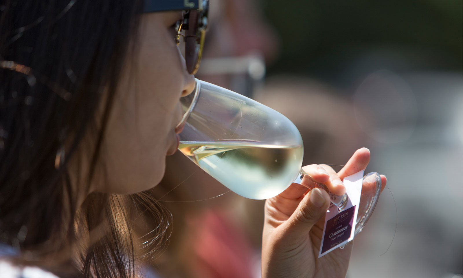 Woman sips wine before her vineyard tour