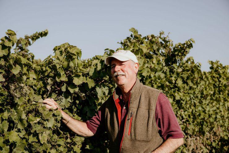 Owner Scott Osborn standing by vineyards at Fox Run
