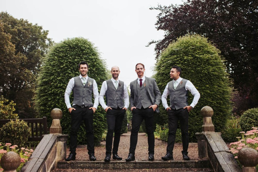 Alternative groomsmen in grey waistcoats with black skinny jeans at Oakwell Hall
