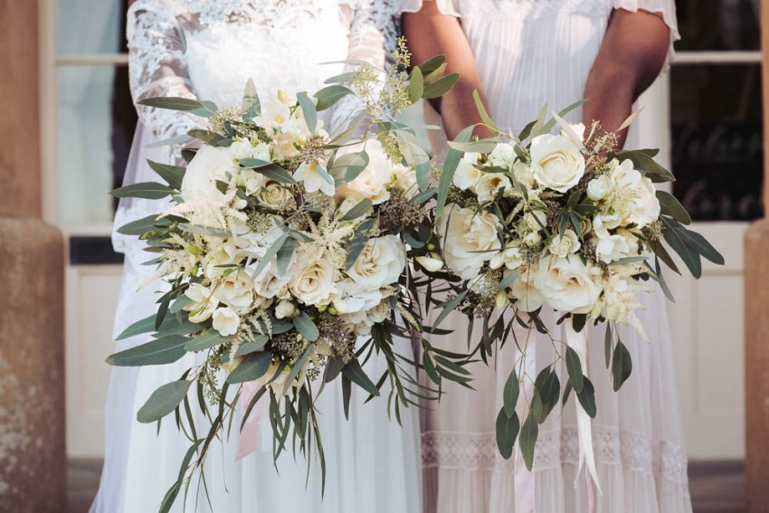Bride and brides maid hold wedding bouquets containing a mixture of delicate white flowers with eucalyptus foliage at Saltmarshe Hall wedding