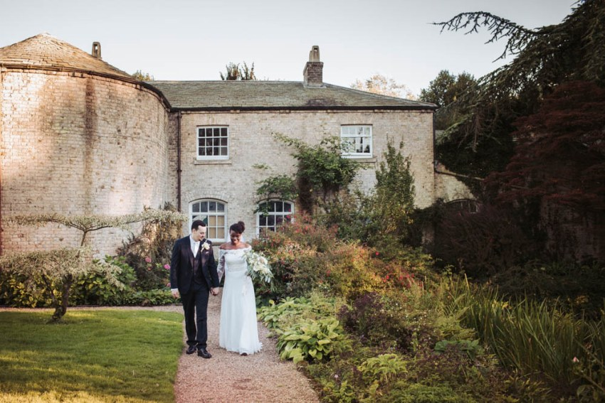 Natural wedding photography at Saltmarshe Hall gardens in East Yorkshire | bride and groom taking a walk
