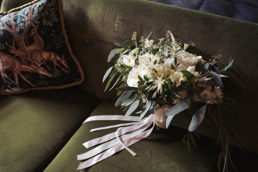 White wedding flowers on green velvet sofa