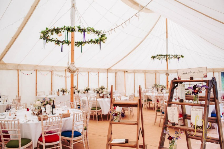 Marquee decorated for wedding at Markington Hall in Yorkshire with rustic themed florals.