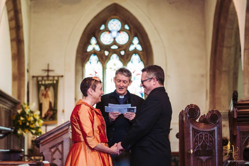 Vicar blesses couple. Bride wears orange dress for renewal of wedding vows. at Linton St. Michael's church in Grassington, Yorkshire.