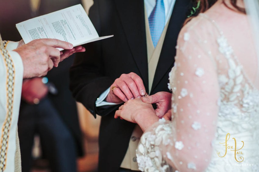 Groom places ring on brides finger at St. Joseph's church in Bishop Thornton, North Yorkshire.