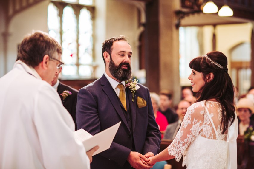 Bride and groom hold hands during wedding ceremony at St. Paul's church in Shipley