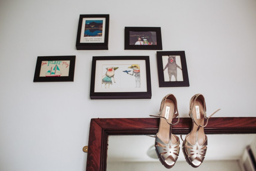 Gold lame wedding shoes hung on mirror below framed pictures.