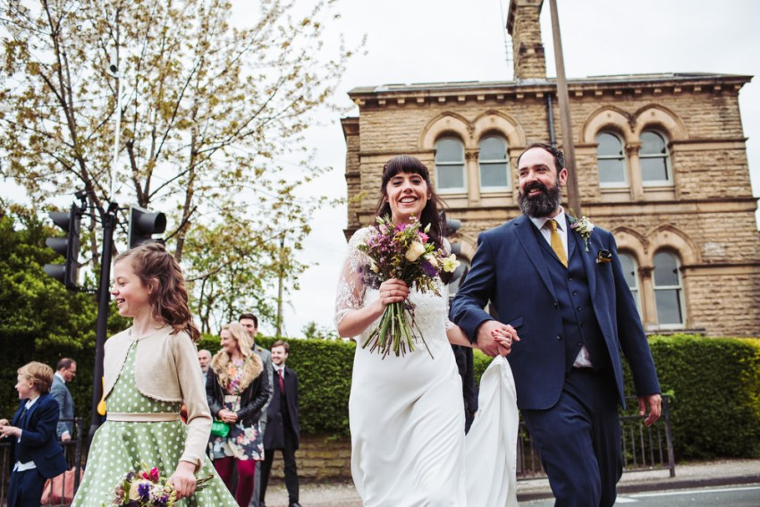 Victoria Hall wedding, Saltaire Yorkshire. Bride and groom walk with wedding guests.
