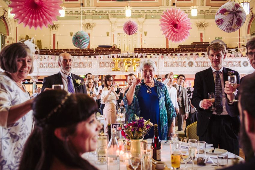 Guests raise their glasses to toast to the bride and groom.
