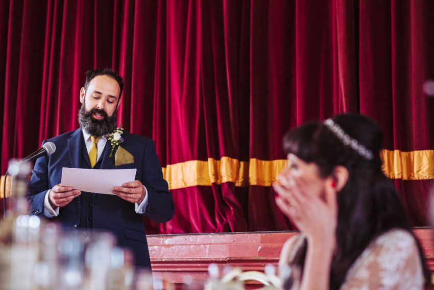 Groom makes his speech as bride wipes a tear from her eye