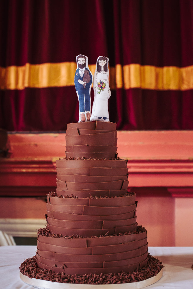 Chocolate wedding cake with fabric printed cake topper of illustration of bride and groom.