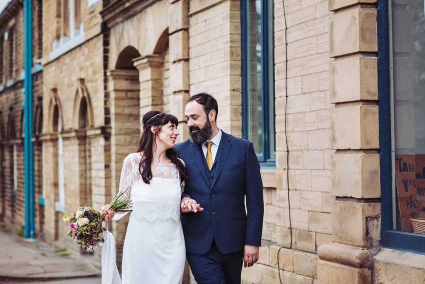 Yorkshire Victoria Hall wedding photographer, Saltaire. Bride and groom walk hand in hand along the street.