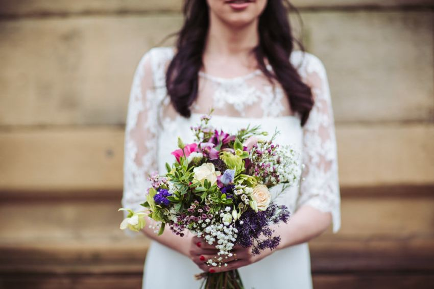 Bride holds bouquet at Victoria Hall wedding in Saltaire.
