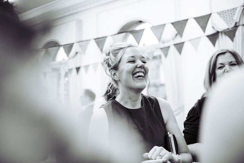 Documentary wedding photography of guests laughing.