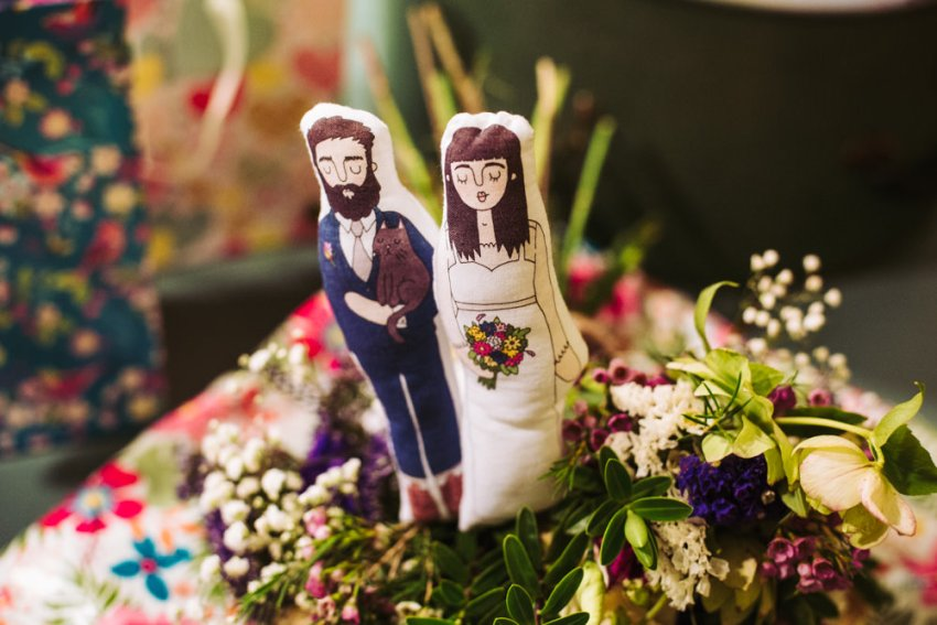 Fabric printed cartoon cake toppers of bride and groom placed in wedding bouquet.