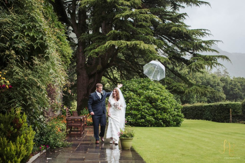 New Dungeon Ghyll wedding photography in the Lake District rain | Groom throws umbrella in the air