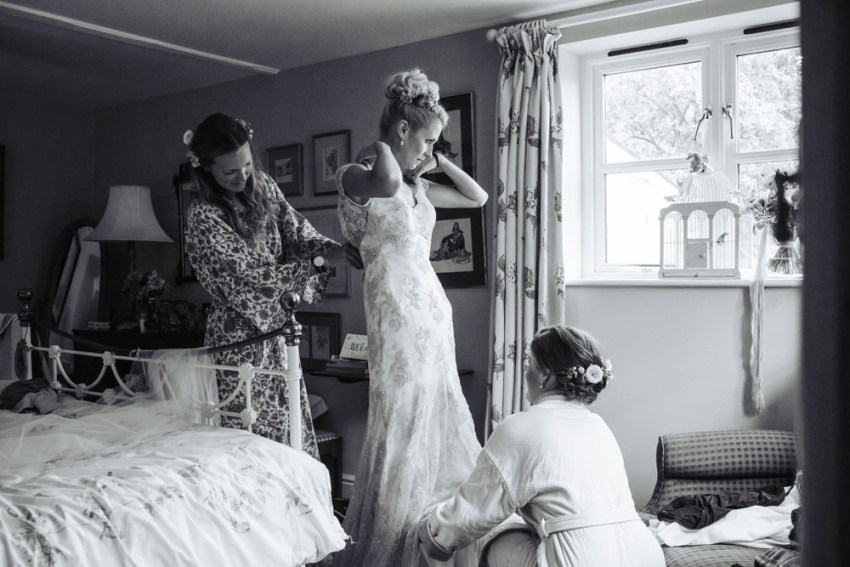 Bridesmaids help the bride into her Liliana Dabic gown.