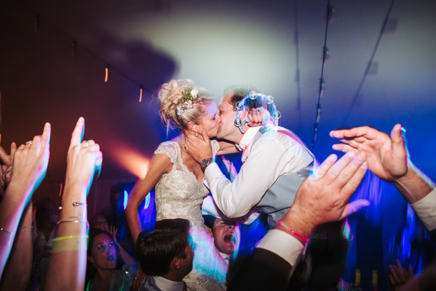 Bride and groom are lifted in the air by guests on the dance floor. Harrogate wedding photographer UK.