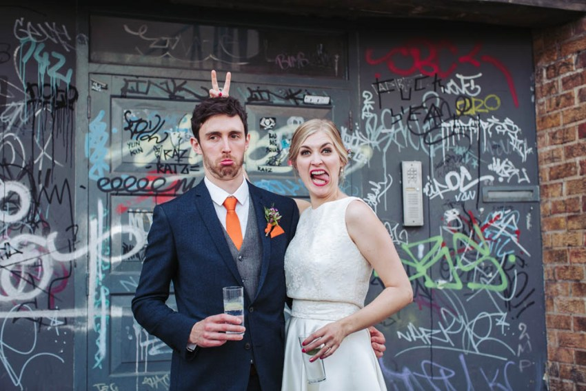 Trafalgar Warehouse wedding photography Sheffield Yorkshire. Bride and groom pull faces in graffiti doorway.