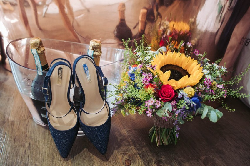 Brides navy blue sparkly shoes and bridal bouquet with sunflowers.