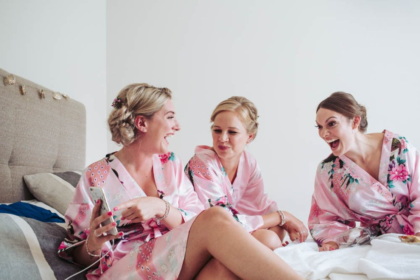 Bridesmaids sat on bed laughing wearing pink kimono style dressing gowns.